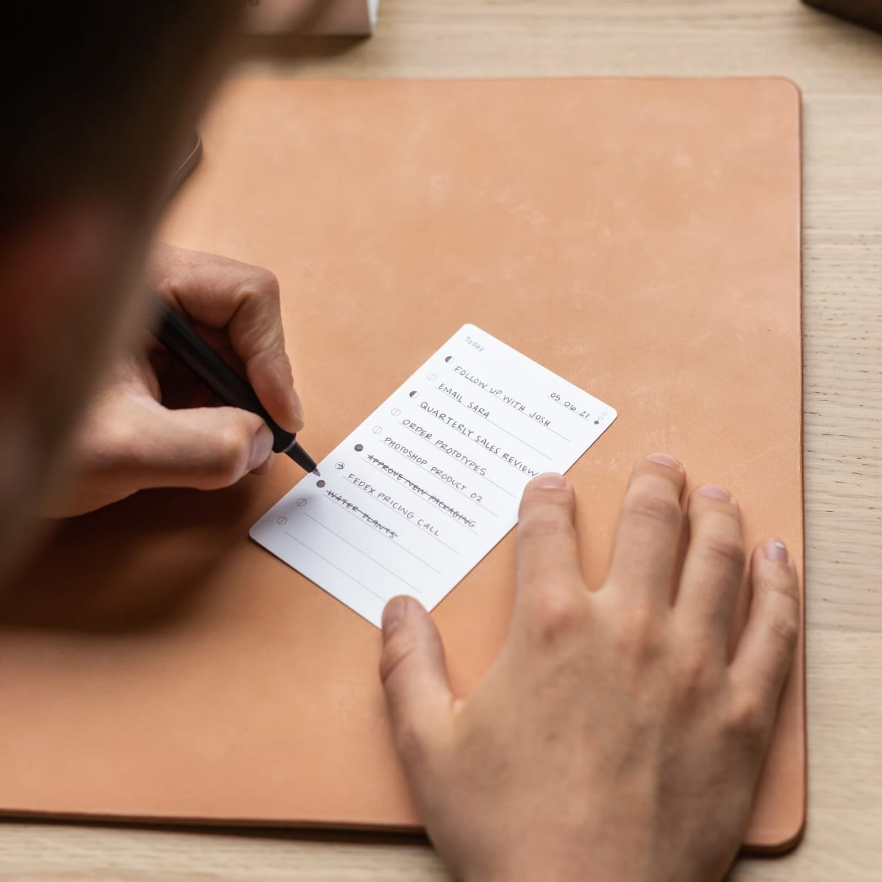 Person using a pen to cross a task off a productivity paper card.