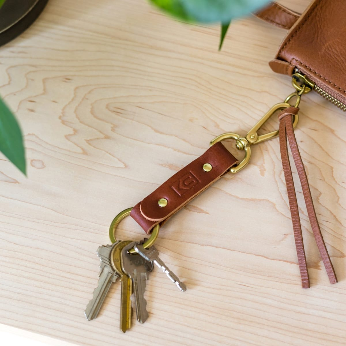 Brown leather key ring with brass metal loops and rivets on wood table.