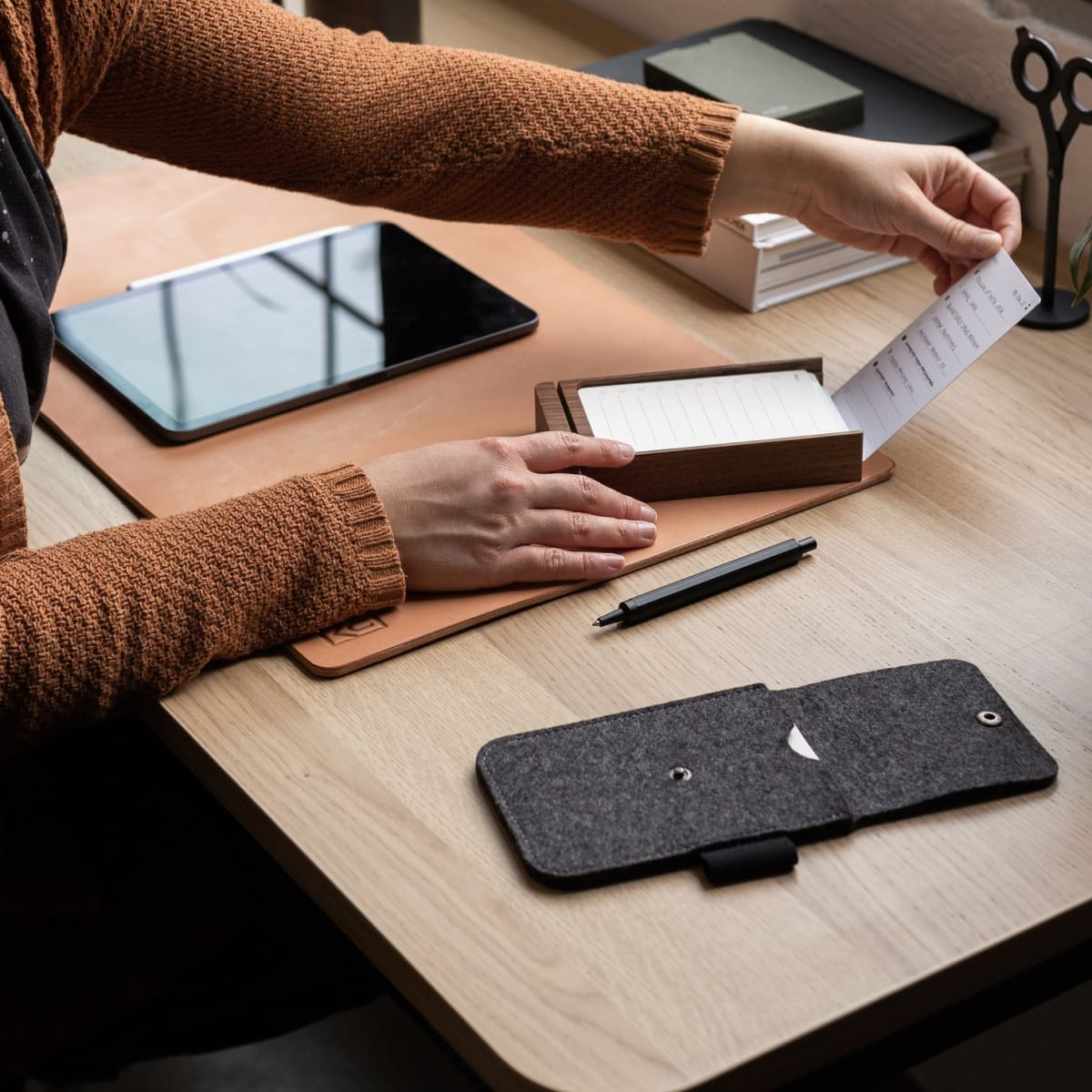 Person placing task list card into walnut card holder next to felt carrying case on leather desk pad.