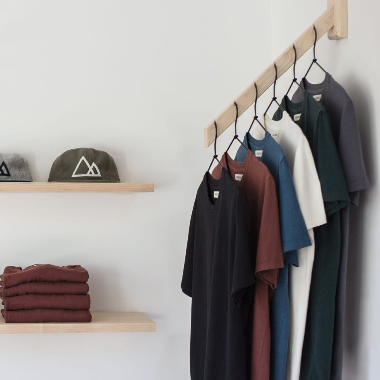 Hats and sweaters on wood shelves next to various colors of t-shirts on hangers.