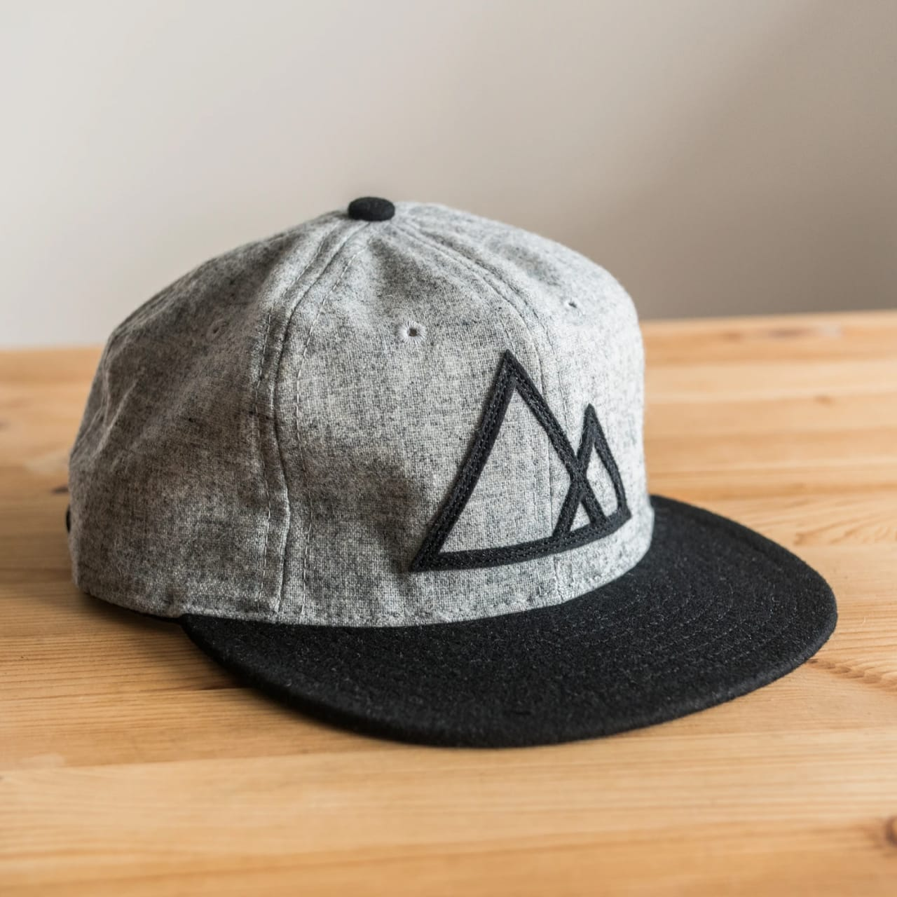 Grey 6-panel baseball hat with black brim, black mountain graphic on front, and light heather gray body.