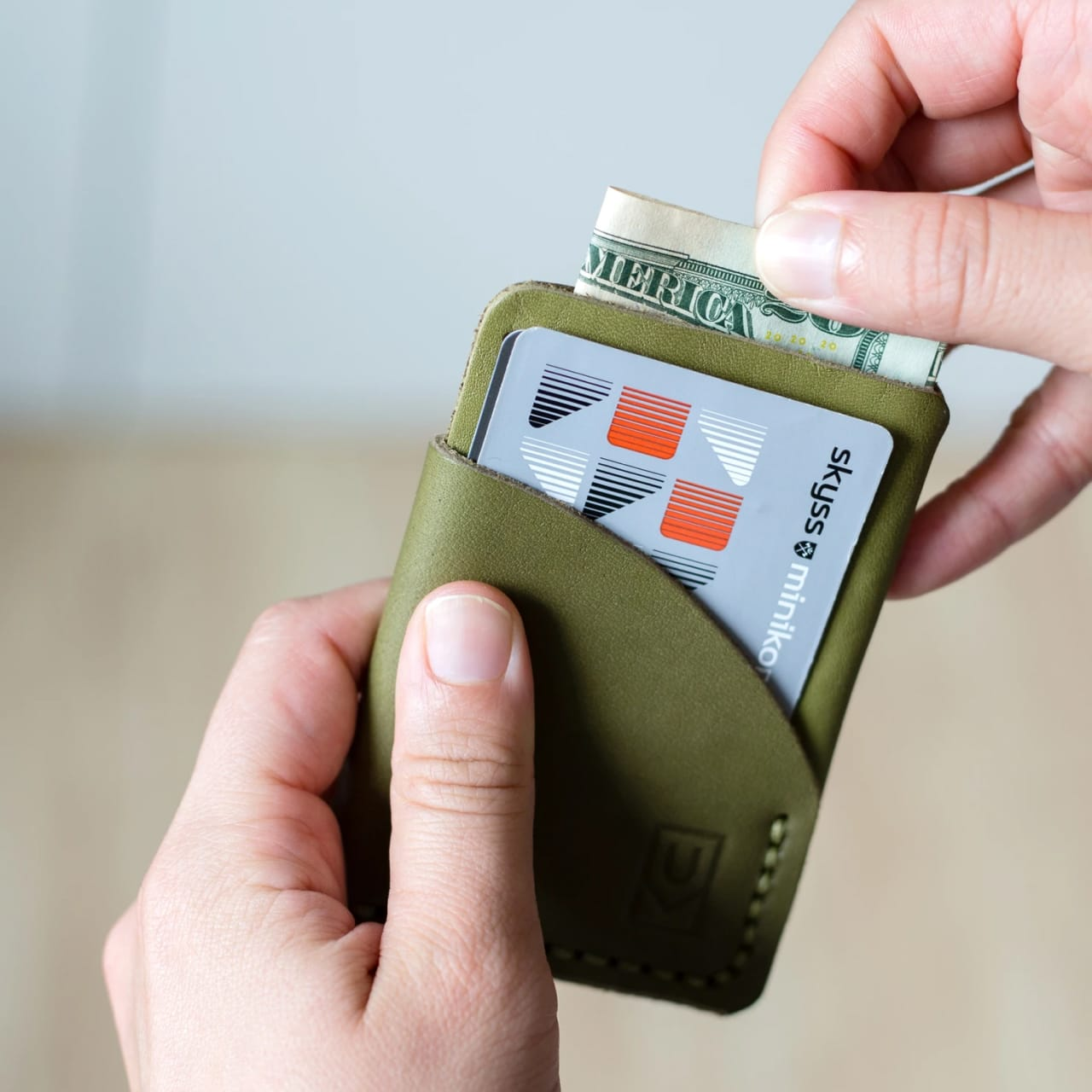 Model putting folded cash into slim card holder olive leather wallet with hand stitching.