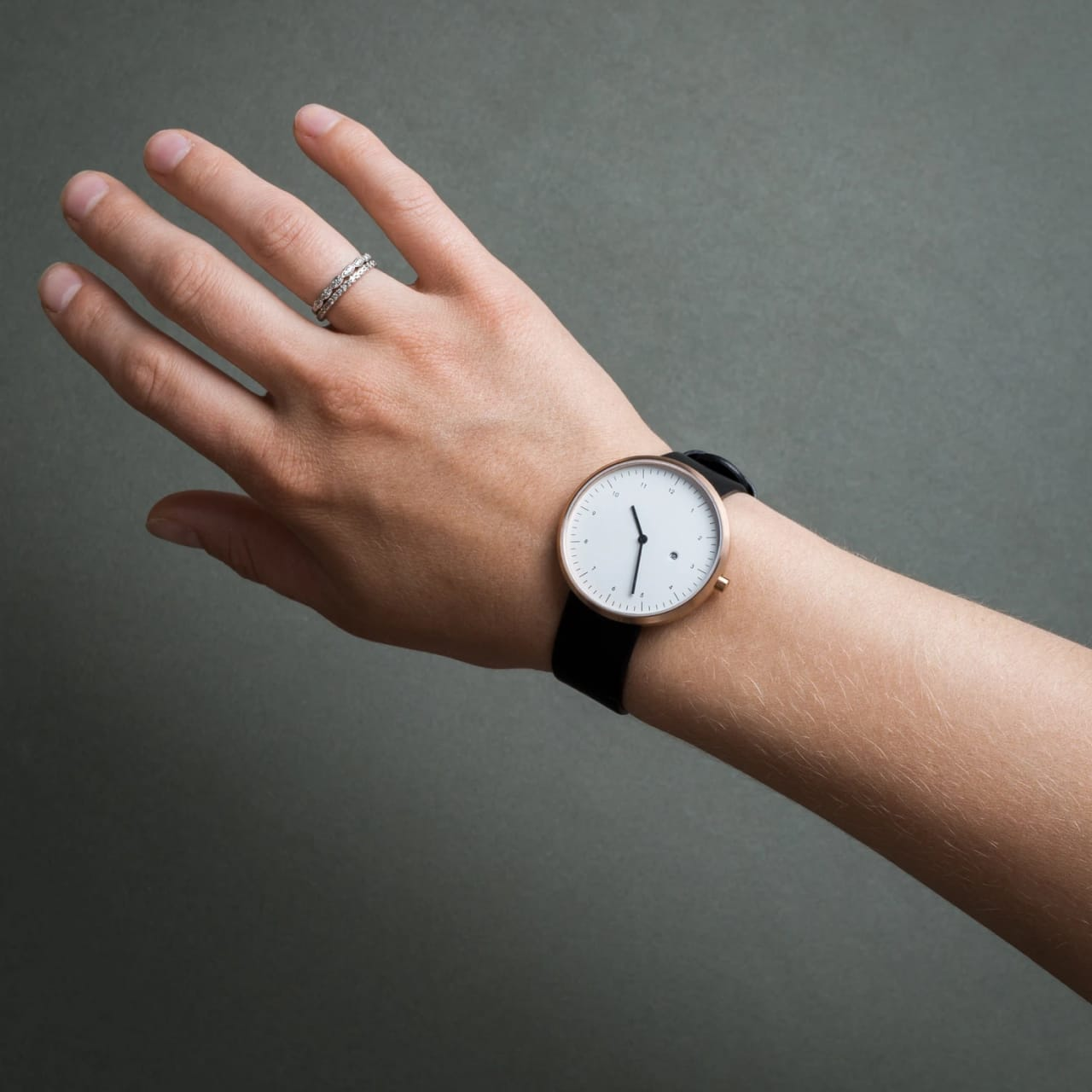 Model wearing minimalist watch with black wristband and white watch face.
