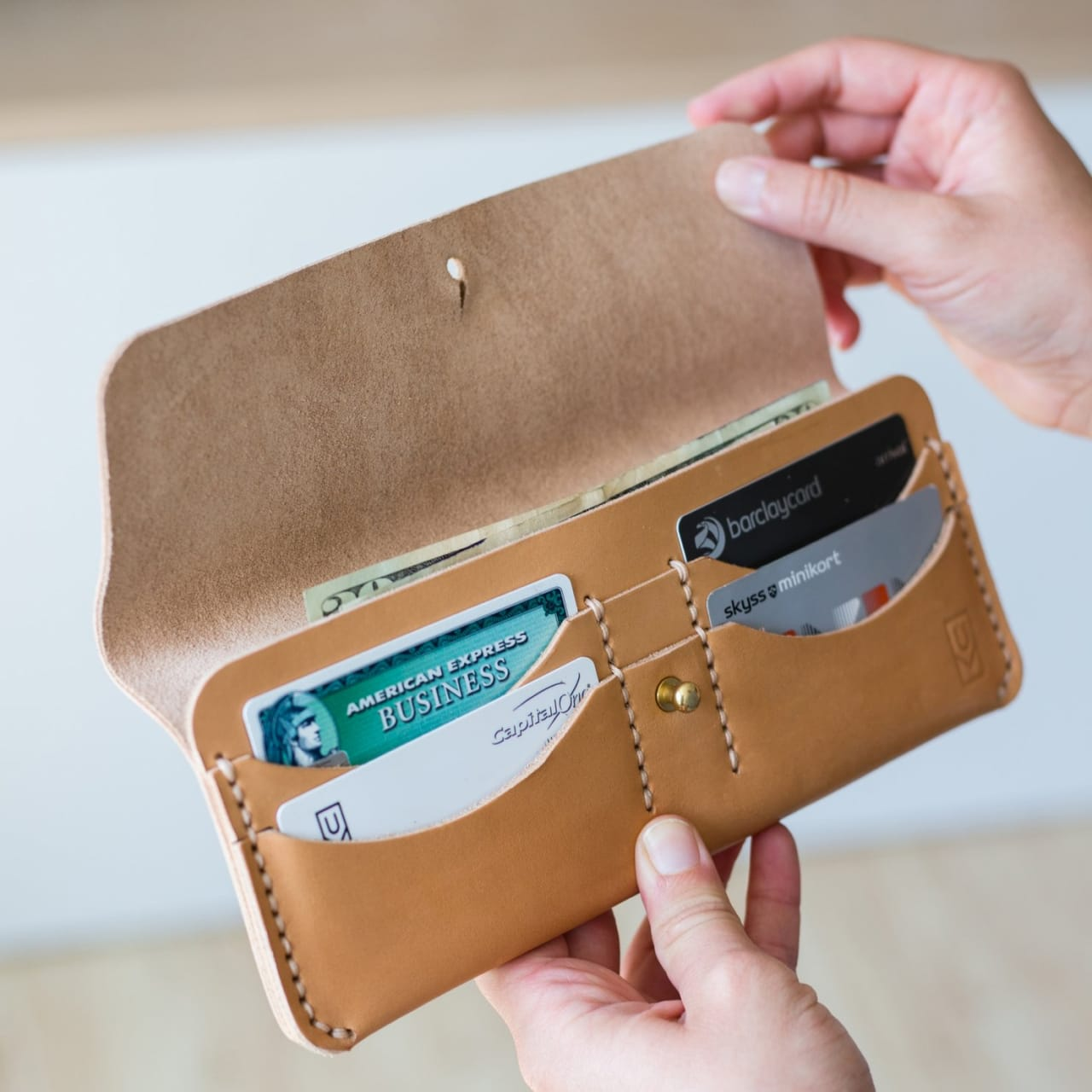 Model opening tan leather long wallet with credit card pockets and cash pouch.